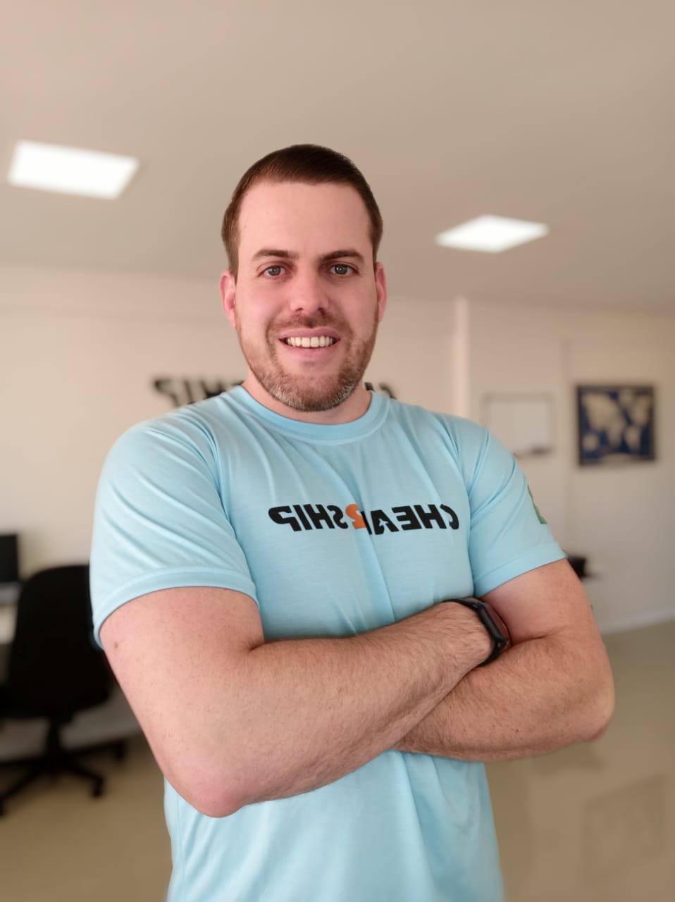 Na foto há Jociano Motta, CEO da CEO da Cheap2Ship, com uma camiseta azul que contém a logo da empresa.